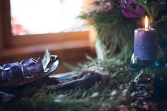Bouquet of flowers in a vase, candles on a tray, vintage home decor on an a table, dark tones. Purple stock photo