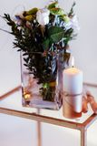 Bouquet of flowers in a vase, candles on a tray, vintage home decor on an a table. Ouquet of white flowers in a vase, candles on vintage copper tray, wedding stock photography