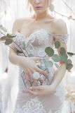Bouquet of flowers in a vase holding a girl bride in an elegant white wedding dress with a big ring on his finger Royalty Free Stock Photography