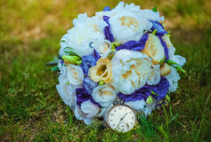 A bouquet of flowers with a vintage, pocket watch lying on the grass in the park. Royalty Free Stock Photo