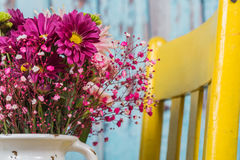 Bouquet of flowers in vintage vase sitting on yellow chair Stock Image
