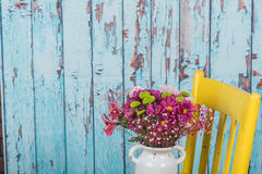 Bouquet of flowers in vintage vase sitting on yellow chair Stock Photos