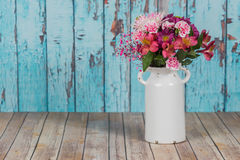 Bouquet of flowers in vintage white vase in rustic setting Royalty Free Stock Images