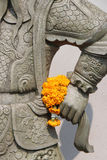 A bouquet of flowers was placed in the hand of the statue of a warrior (Thailand) Stock Images