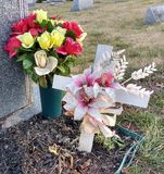 Bouquet of Flowers and White Cross in a Cemetery Stock Photo