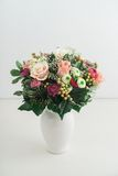 Bouquet of flowers. In a white vase on a white table stock image
