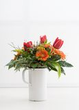 Bouquet of flowers. In a white vase on a white table royalty free stock photography