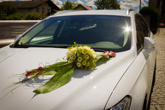 Bouquet of flowers on white wedding car, wedding day. Royalty Free Stock Photo