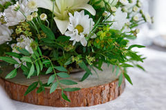 Bouquet of flowers on wood. Bouquet of white and green flowers on brown circle made of wood Stock Photography
