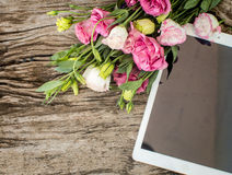 Bouquet of flowers on a  wooden table with a tablet computer wit Royalty Free Stock Photos