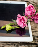 Bouquet of flowers on a  wooden table with a tablet computer wit Royalty Free Stock Images