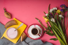 Bouquet of flowers, yogurt, cup of coffee on a pink table Stock Photo