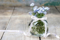 Bouquet of forget-me-not flowers in glass vase Stock Photography