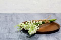 Bouquet of fragrant spring May lily of the valley on brown ceramic dish on black concrete background against white concrete wall. stock photos