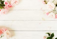 Bouquet frame of beautiful pink roses on white wooden background royalty free stock photos
