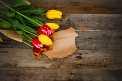 Bouquet of fresh colorful tulips over rustic wooden background. Royalty Free Stock Photos