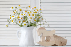 Bouquet of fresh daisies in white jug on wooden background Royalty Free Stock Images