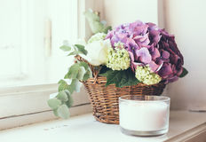 Bouquet of fresh flowers. Big bouquet of fresh flowers, purple hydrangeas and white roses in a wicker basket on a windowsill, home decor, vintage style stock images