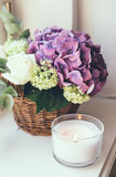 Bouquet of fresh flowers. Big bouquet of fresh flowers, purple hydrangeas and white roses in a wicker basket on a windowsill, home decor, vintage style royalty free stock image