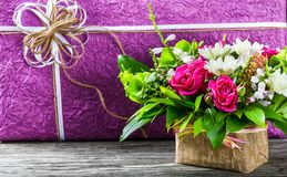 Bouquet of fresh flowers and gift box on an old wooden table Stock Photography