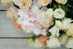 Bouquet of fresh flowers. A bouquet of fresh flowers lies in the right corner on wooden boards Stock Photo