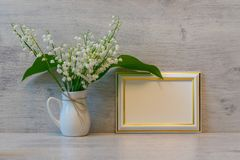 Bouquet of fresh lilies of the valley flowers and empty photoframe on light wooden background. Beautiful spring still life, mock. Bouquet of fresh lily of the royalty free stock images