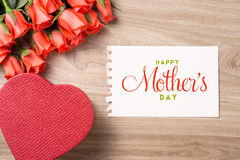 Bouquet of fresh pink red roses with gift on wooden background. Floral romantic arrangement with card text Happy Mother's Day Stock Photo