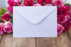 A bouquet of fresh pink roses on a wooden table. The message is in a white envelope. Free space for text or postcards. royalty free stock image
