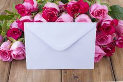 A bouquet of fresh pink roses on a wooden table. The message is in a white envelope. Free space for text or postcards royalty free stock photos