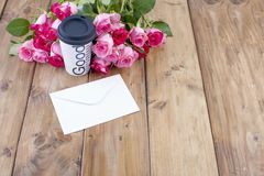 A bouquet of fresh pink roses on a wooden table. The message is in a white envelope. Free space for text or postcards royalty free stock image