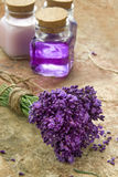 Bouquet of fresh purple flowers and bottles of soap and lotion Stock Photos