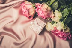 Bouquet of fresh roses and a gift on the background of silk fabric. Copy space. Celebratory concept royalty free stock images