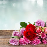 Bouquet of fresh roses and ranunculus. Bouquet of roses and ranunculus on wood border with copy space on blue bokeh background Stock Image