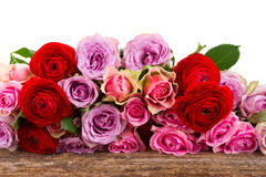 Bouquet of fresh roses and ranunculus. On wood border isolated on white background Royalty Free Stock Image