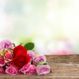 Bouquet of fresh roses and ranunculus. Bouquet of roses and ranunculus on wood with copy space on bokeh background Stock Images