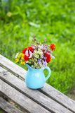 Bouquet of fresh summer flowers in a blue ceramics vase on wooden bench. Bouquet of fresh bright summer flowers in a blue ceramics vase on wooden bench royalty free stock image
