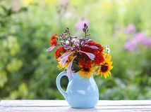 Bouquet of fresh summer flowers in a blue ceramics vase on wooden bench stock images