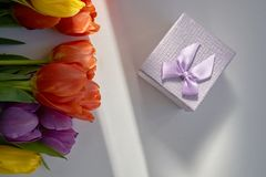 Bouquet of fresh tulips illuminated by sun ray and a gift box lying on the wooden table. Gift for a Valentine`s day, birthday,wedding,woman`s day,mother`s day Stock Photography