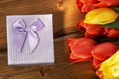 Bouquet of fresh tulips illuminated by sun ray and a gift box lying on the wooden table. Gift for a Valentine`s day, birthday,wedding,woman`s day,mother`s day Royalty Free Stock Images
