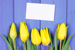 Bouquet of fresh tulips on purple wooden background, copy space for text on sheet of paper Stock Image