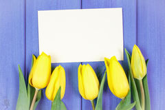 Bouquet of fresh tulips on purple wooden background, copy space for text on sheet of paper Stock Photo
