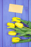 Bouquet of fresh tulips on purple wooden background, copy space for text on sheet of paper Royalty Free Stock Image