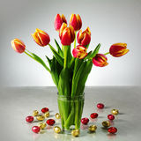 bouquet of fresh tulips and small red yellow chocolate easter eggs on the table, spring decoration royalty free stock images