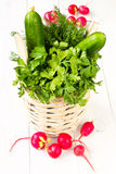 A bouquet of fresh vegetables in a bowl wicker basket on white w. A bouquet of fresh different vegetables in a bowl wicker basket on white wooden background Royalty Free Stock Image