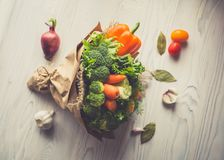 Bouquet of fresh vegetables lies on a white wooden table. Nearby is a red onion, tomatoes, garlic, bay leaf. View from above. Tone Royalty Free Stock Image