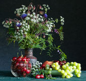 Bouquet and fruits. Still-life with fruits and a bouquet of field colors Stock Image