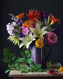 Bouquet of garden flowers in a jug. Still life. Bouquet of garden flowers in the vase, and a branch of a raspberry. Still life Royalty Free Stock Images