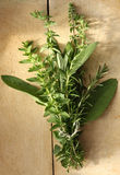 Bouquet Garni. A bouquet garni of fresh-picked herbs, on a weathered old chopping board.  Rosemary, sage, oregano and thyme, tied with string ready for adding to Royalty Free Stock Photography