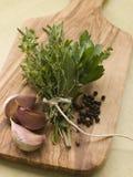 Bouquet Garni Garlic Cloves and Peppercorns. On a chopping board Stock Image