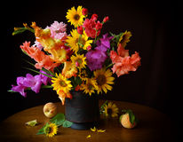 Bouquet of gladioli and sunflowers. Still life with summer flowers, gladioli, sunflowers, fruit, peaches stock images